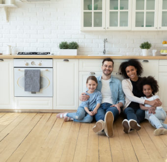 Portrait of multiracial family with kids on kitchen floor